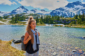 Young beautiful woman hiking near the lake over mountain background