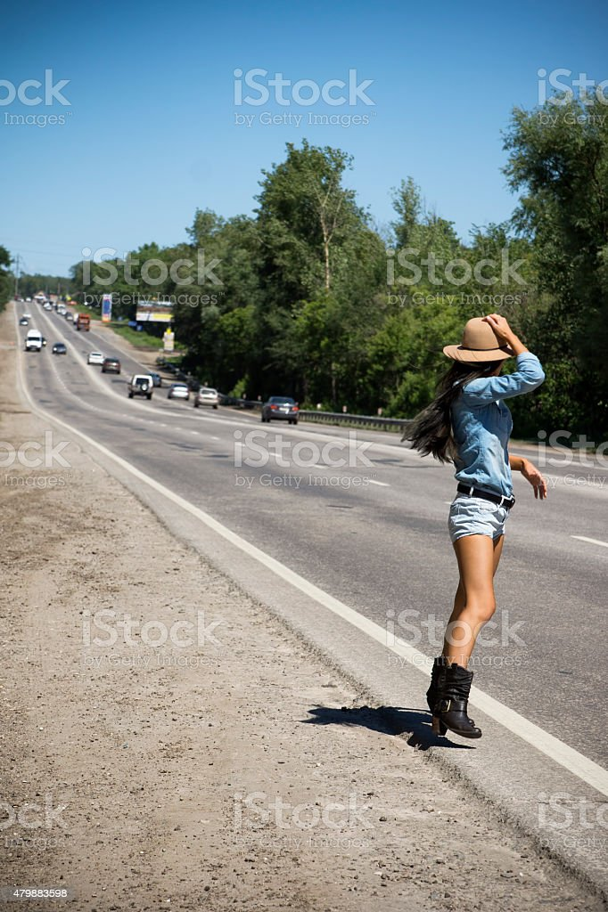 Young beautiful woman hitchhiking along a road stock photo