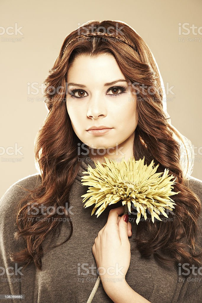 Young beautiful woman holding a yellow flower in her hand royalty-free stock photo