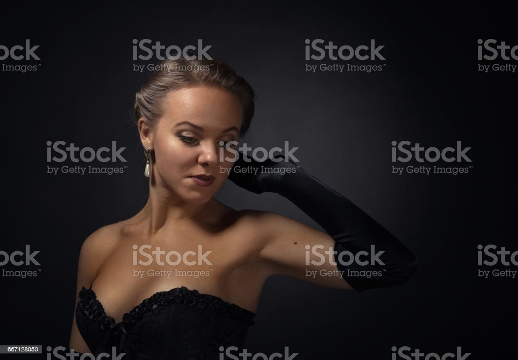 young beautiful woman in black with pearl earrings stock photo