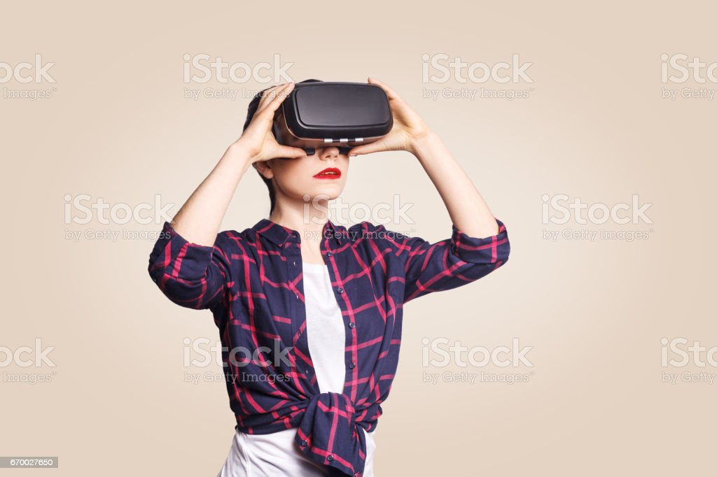 Young beautiful woman in casual style with virtual reality headset on beige background. stock photo