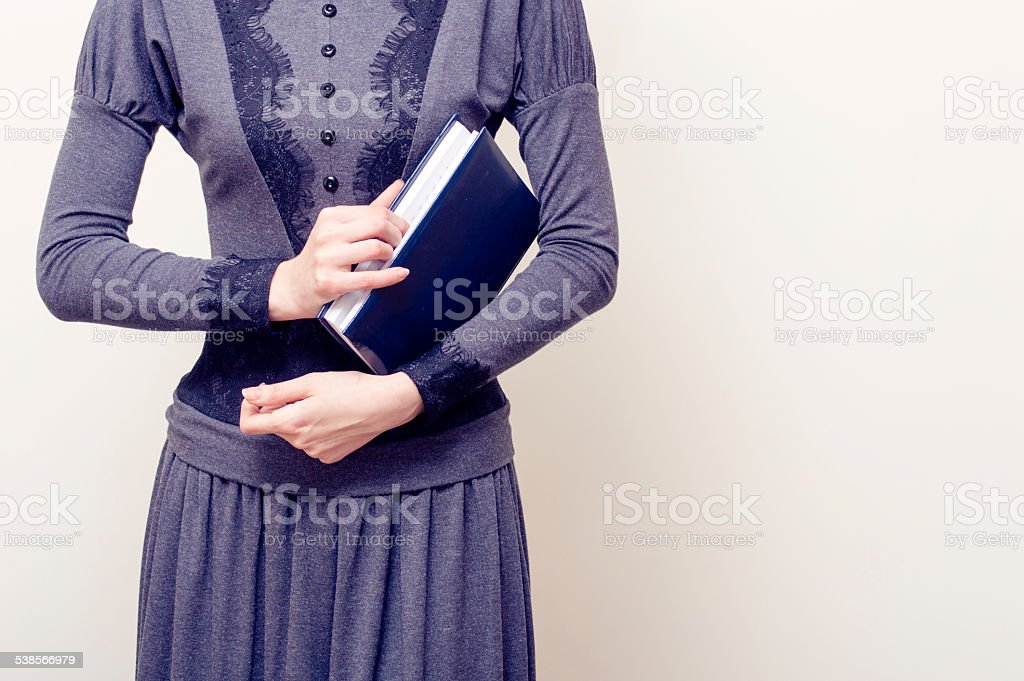 Young beautiful woman in gray vintage dress holding bible stock photo