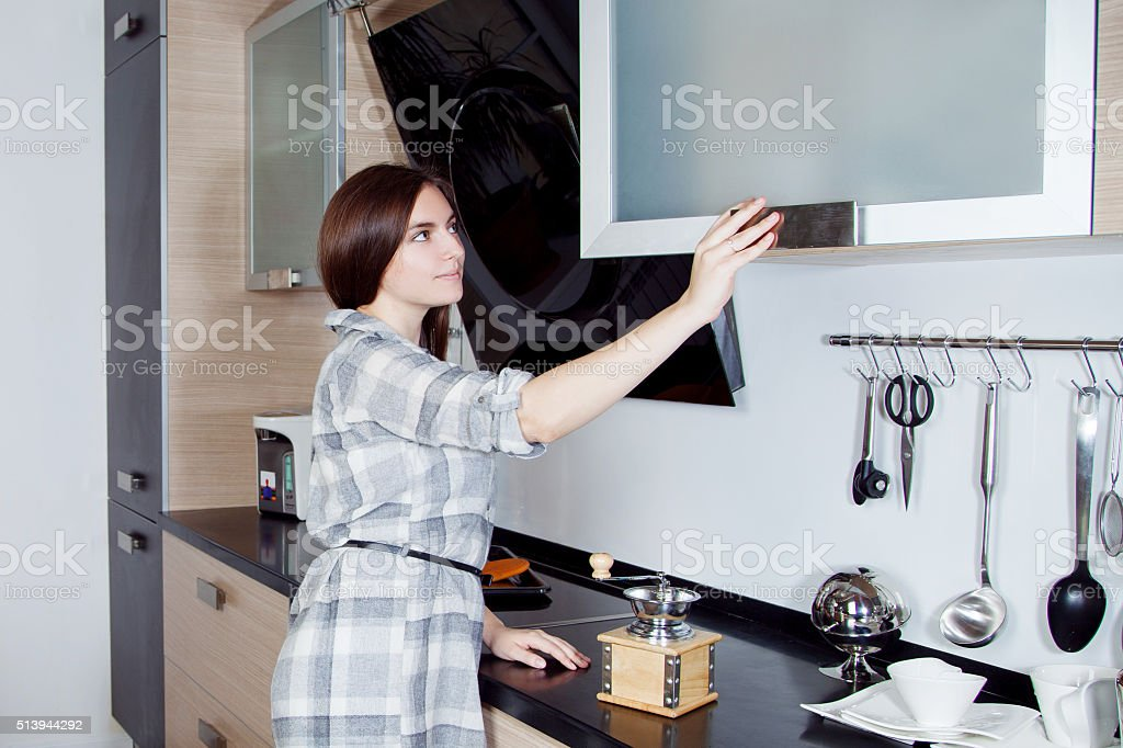 young beautiful woman in kitchen, takes off shelf tools for stock photo