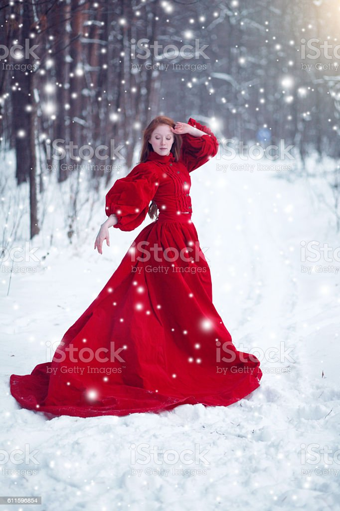 Young beautiful woman in long red dress over winter background. stock photo