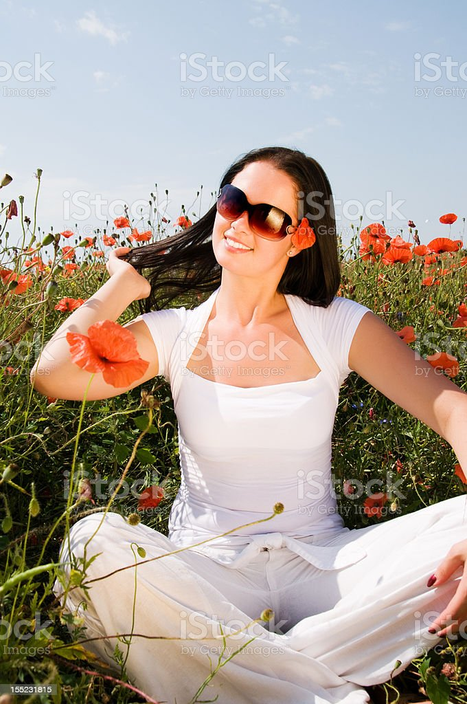 Young beautiful woman in poppy flowers royalty-free stock photo