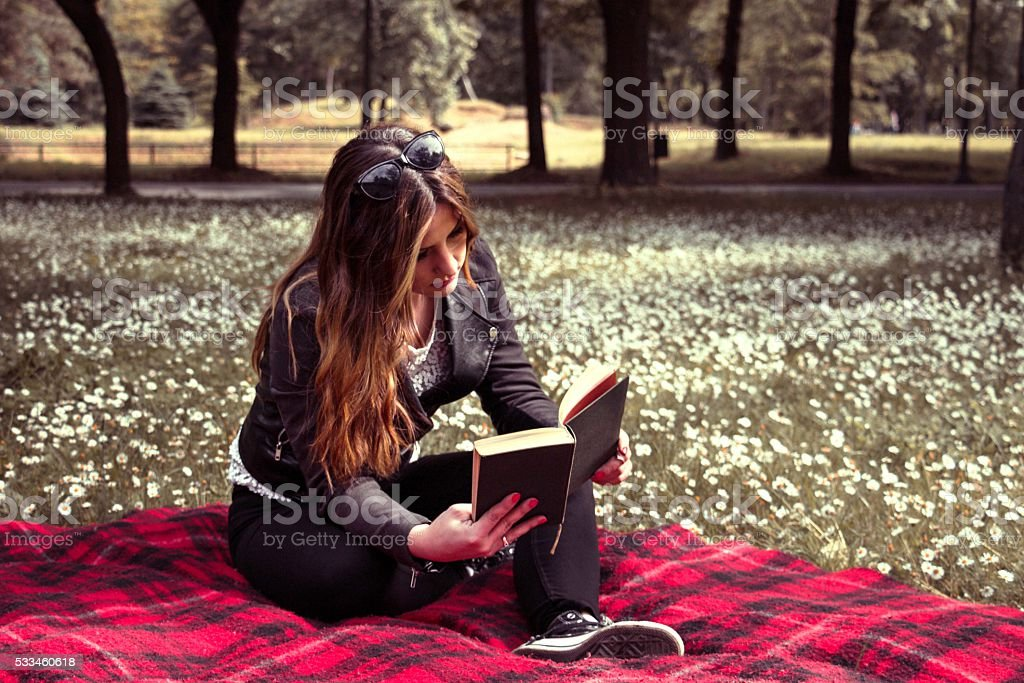 young beautiful woman in summer park reading a book stock photo