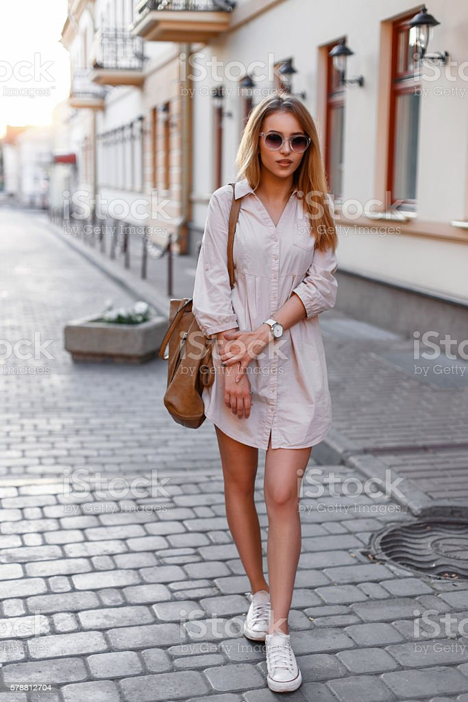 Young beautiful woman in sunglasses, dress and sneakers walking stock photo