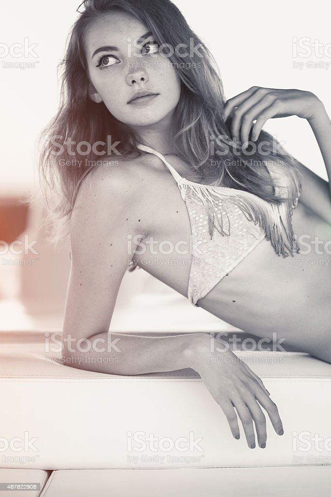 Young beautiful woman in swimsuit posing on yacht stock photo