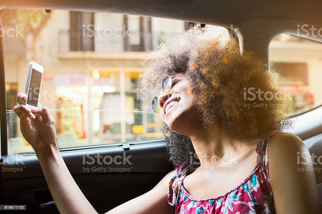 Young beautiful woman in taxi and using a phone stock photo