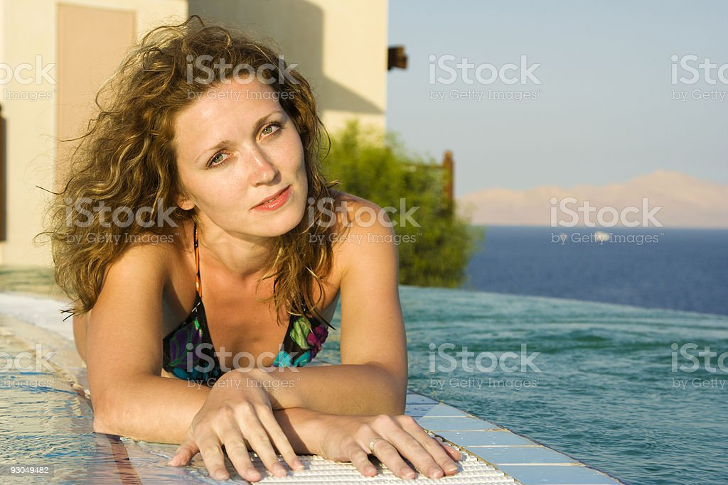 Young beautiful woman laying on edge of infinity pool royalty-free stock photo