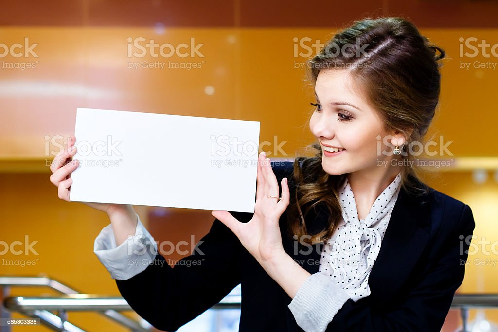 young beautiful woman looking at a blank white card stock photo