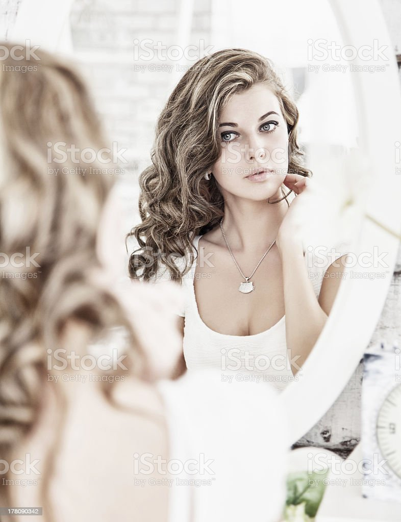 Young beautiful woman looking at her face in the mirror stock photo