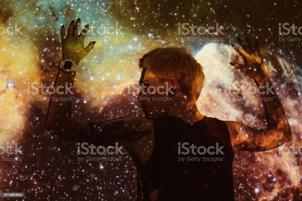 Young beautiful woman lost  in space around stars stock photo