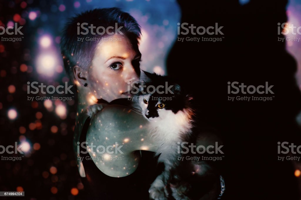 Young beautiful woman lost  in space around stars with cat stock photo