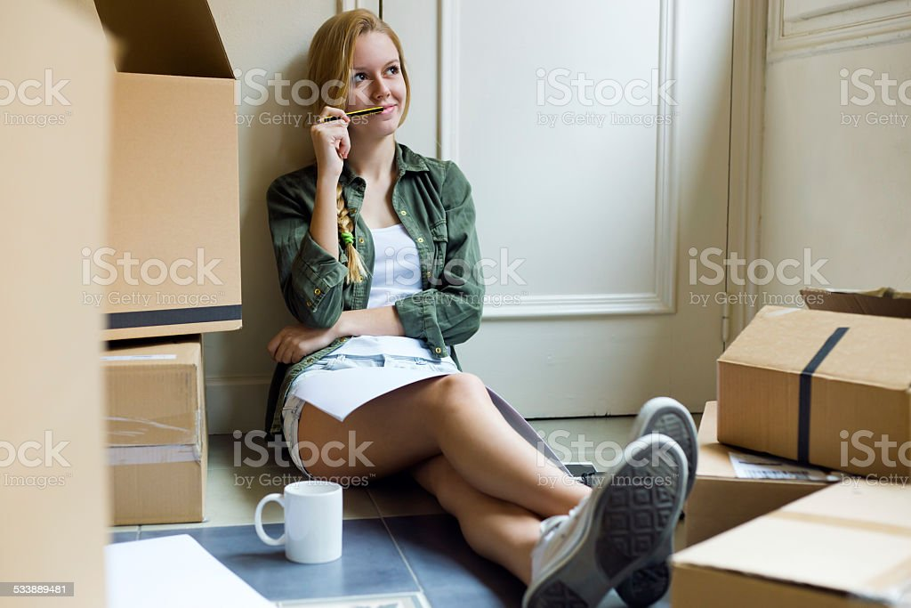 Young beautiful woman moving in new home. stock photo