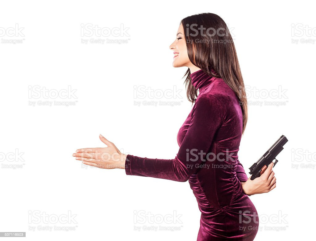 Young beautiful woman offers hand with gun behind her back stock photo