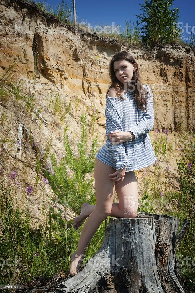Young beautiful woman on stump royalty-free stock photo