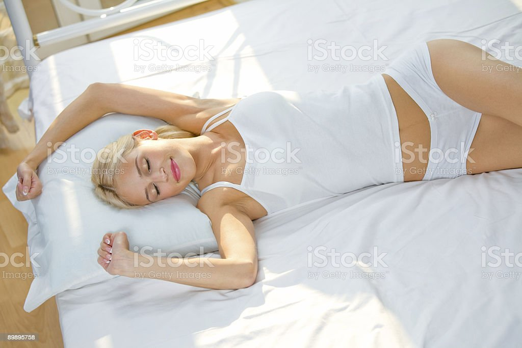 Young beautiful woman on the bed at bedroom royalty-free stock photo