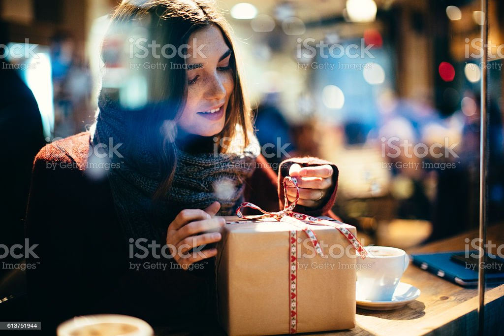 Young beautiful woman opening a present. stock photo