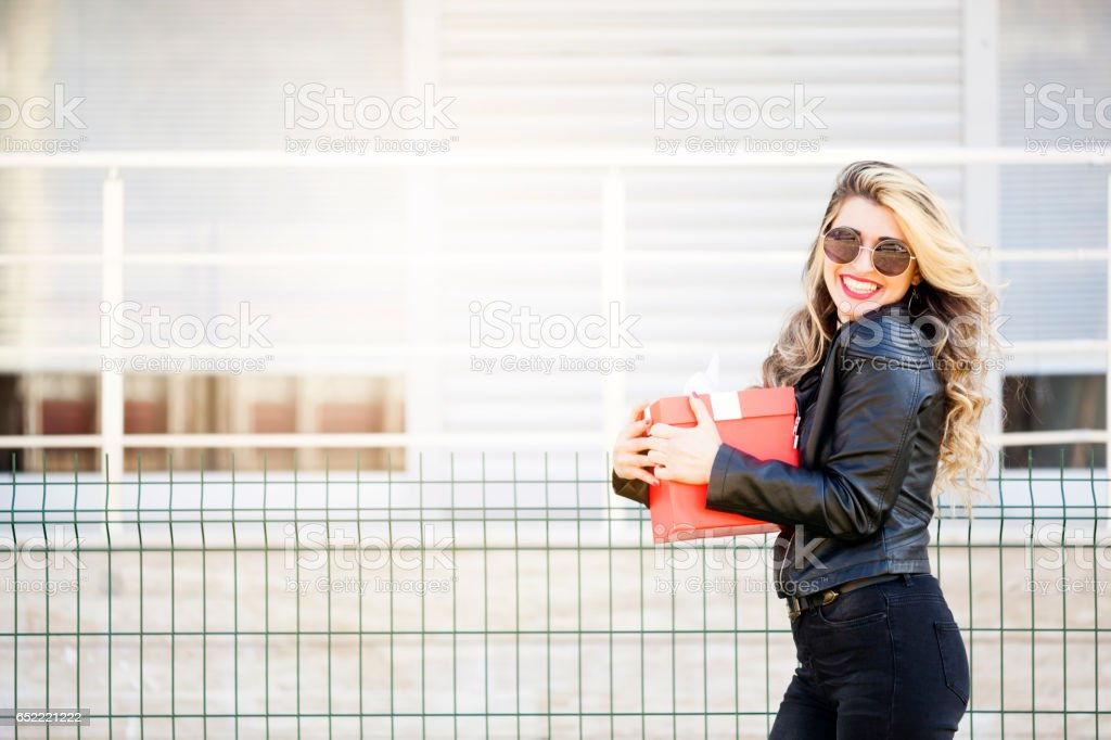 Young beautiful woman opening a present stock photo