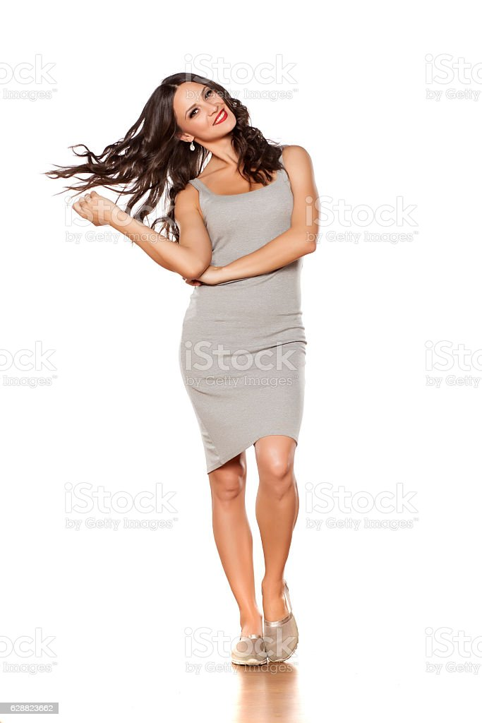young beautiful woman posing in a short dress and espadrille stock photo