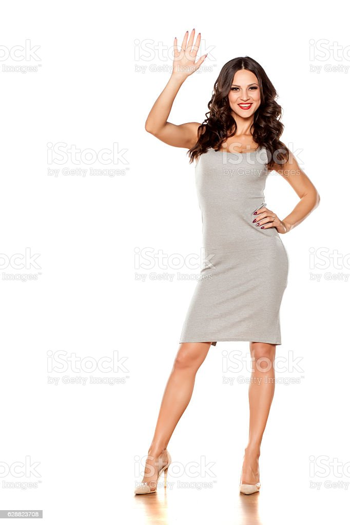 young beautiful woman posing in a short dress waving hand stock photo