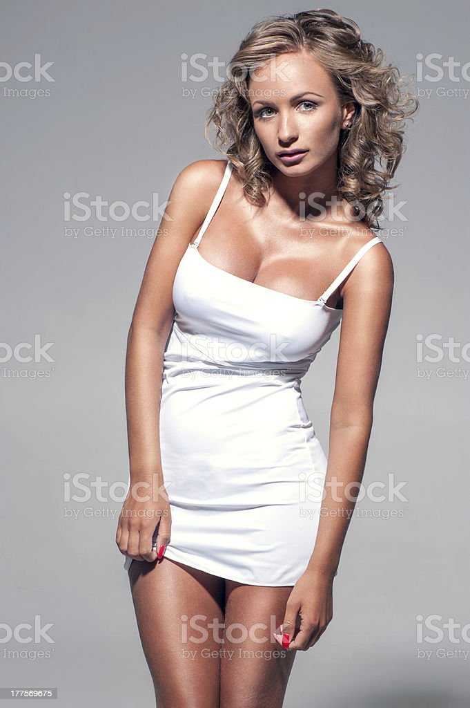 Young beautiful woman posing in white dress stock photo