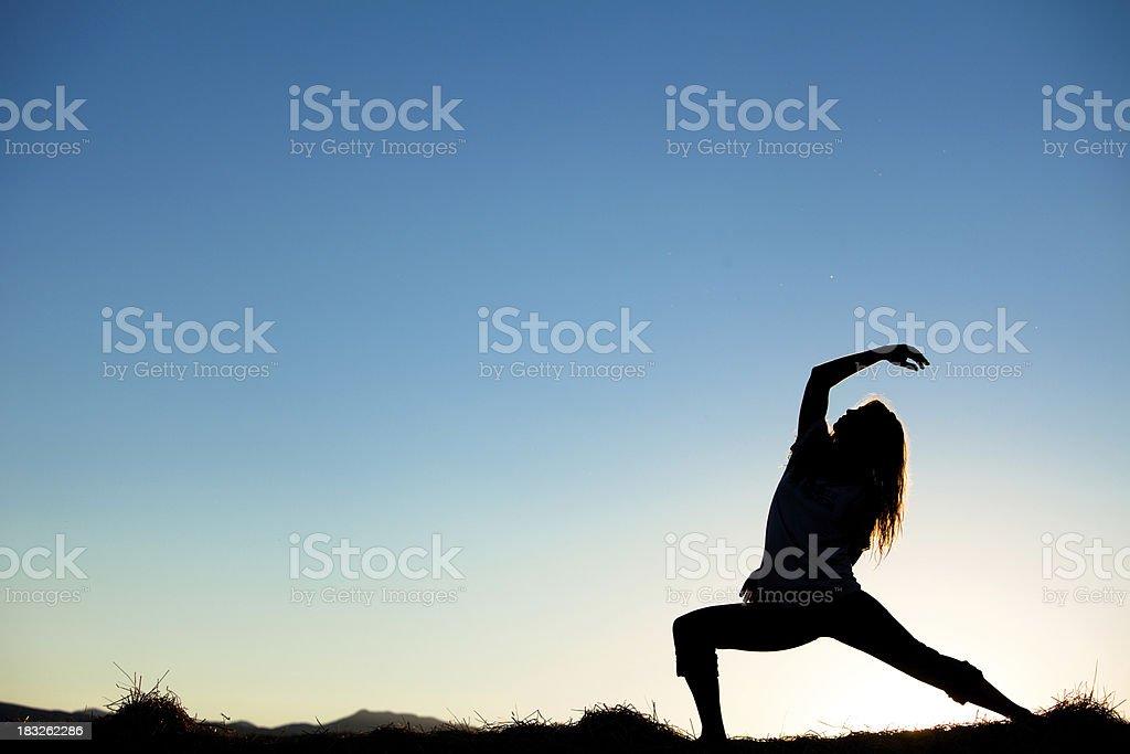 Young beautiful woman practicing yoga at sunset stock photo