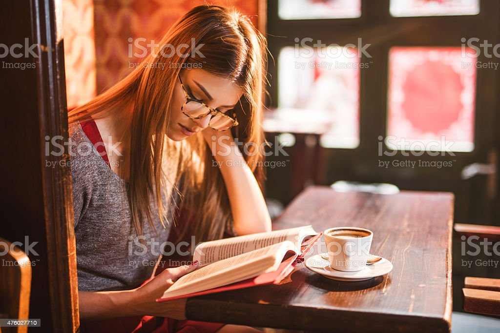 Young beautiful woman reading a book in a cafe. stock photo