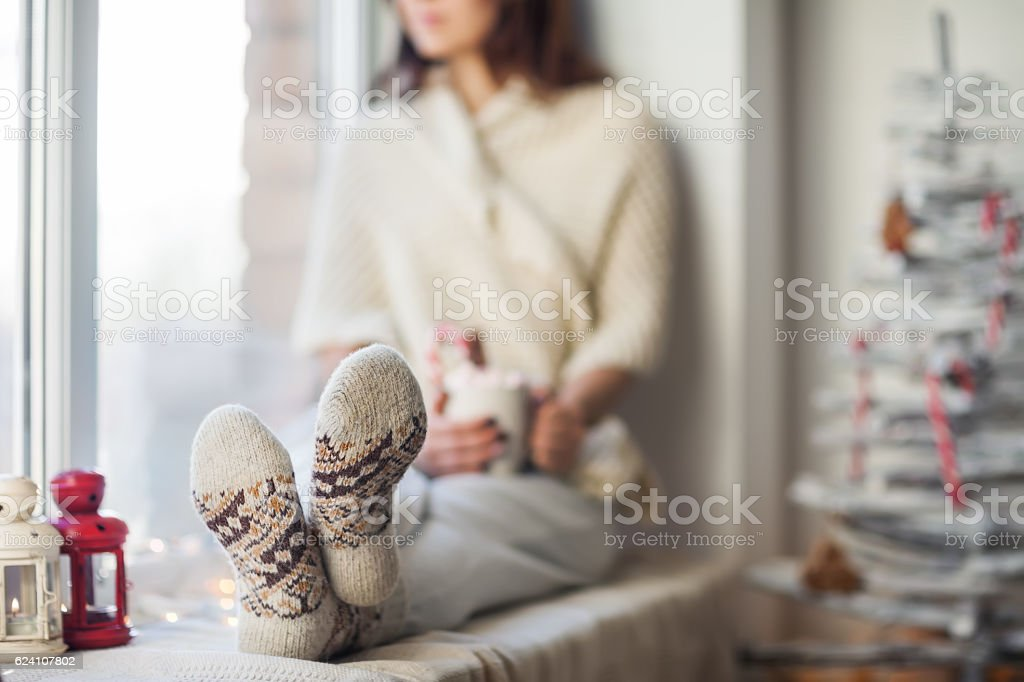 Young beautiful woman relaxing on window sill in christmas decor stock photo