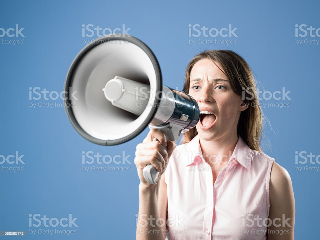 Young Beautiful Woman Shouting Through Megaphone On Sky Blue Background stock photo