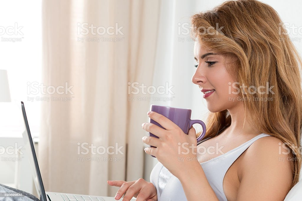 Young beautiful woman sitting at her bedroom with laptop stock photo