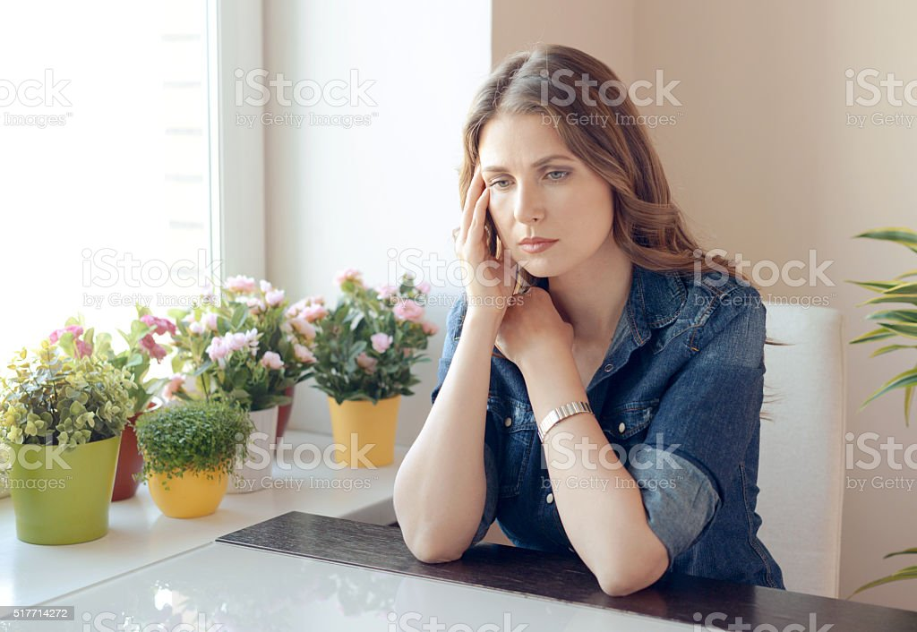 young beautiful woman sitting at the table stock photo