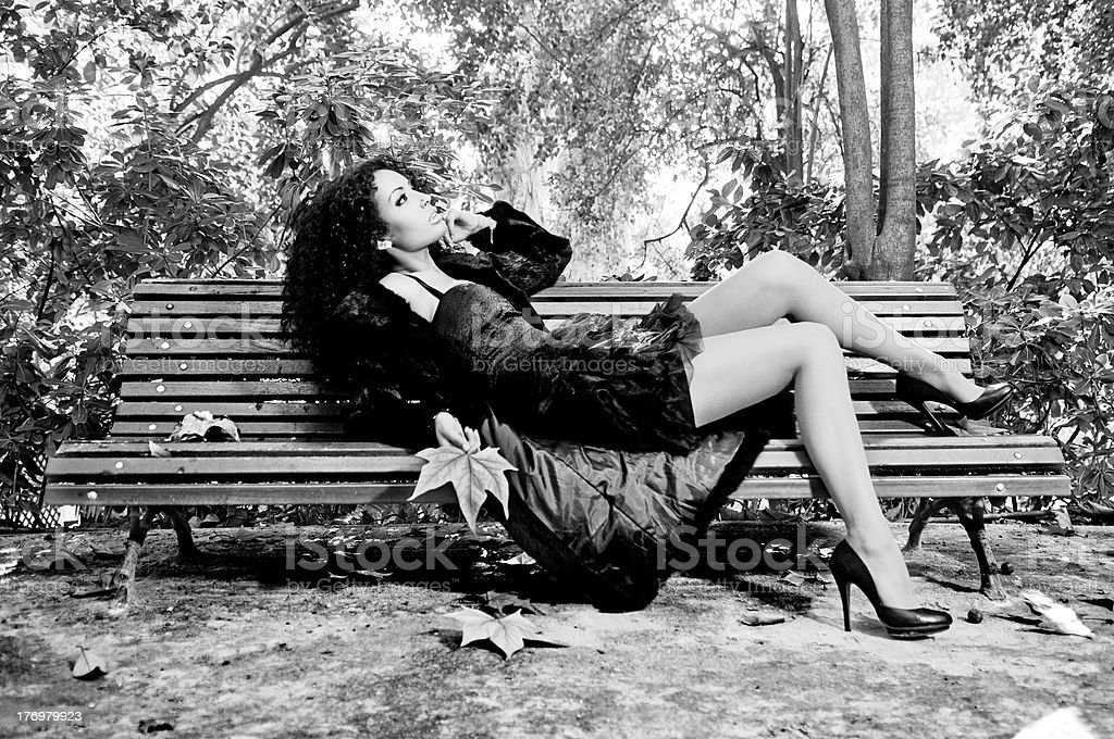 Young beautiful woman sitting on bench in park royalty-free stock photo