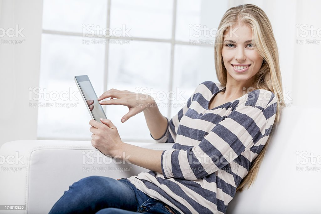young beautiful woman sitting on the couch with tablet pc royalty-free stock photo