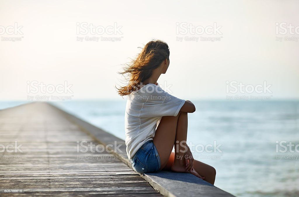 Young beautiful woman sitting on the pier stock photo
