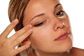 young beautiful woman smearing concealer under the eyes