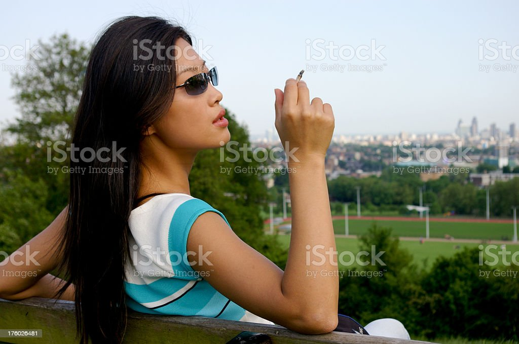 young beautiful woman smoking in park with city view stock photo