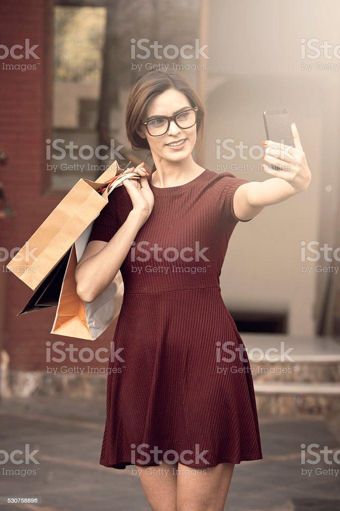 Young beautiful woman taking a selfie while shopping stock photo