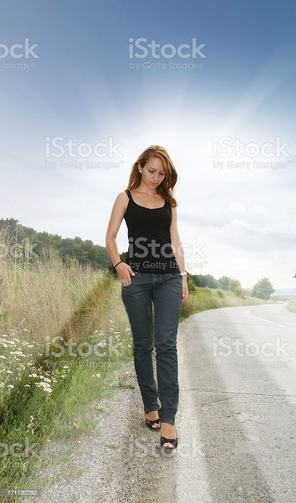 Young beautiful woman walking along street royalty-free stock photo