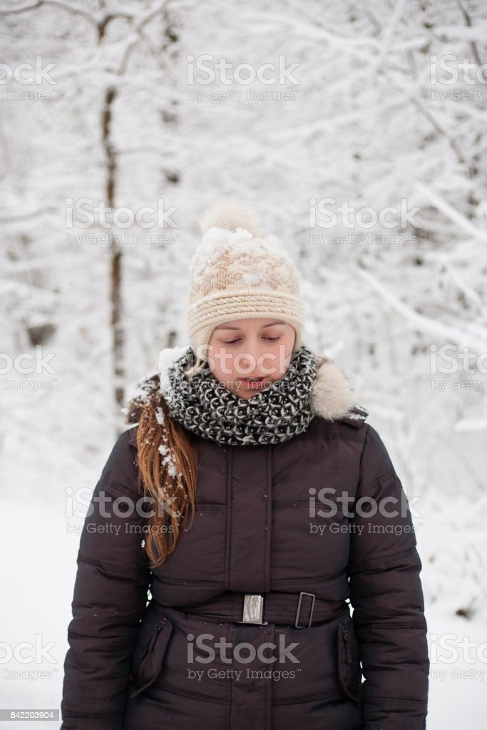 Young beautiful woman walking in a park forest in cold  winter air. Christmas girl. Good weather outdoors stock photo
