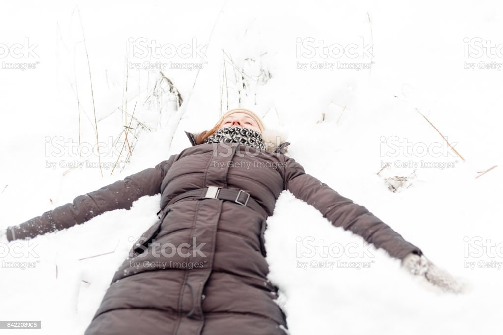 Young beautiful woman walking in a park forest in cold  winter air. Christmas girl. Good weather outdoors. Snow angel stock photo
