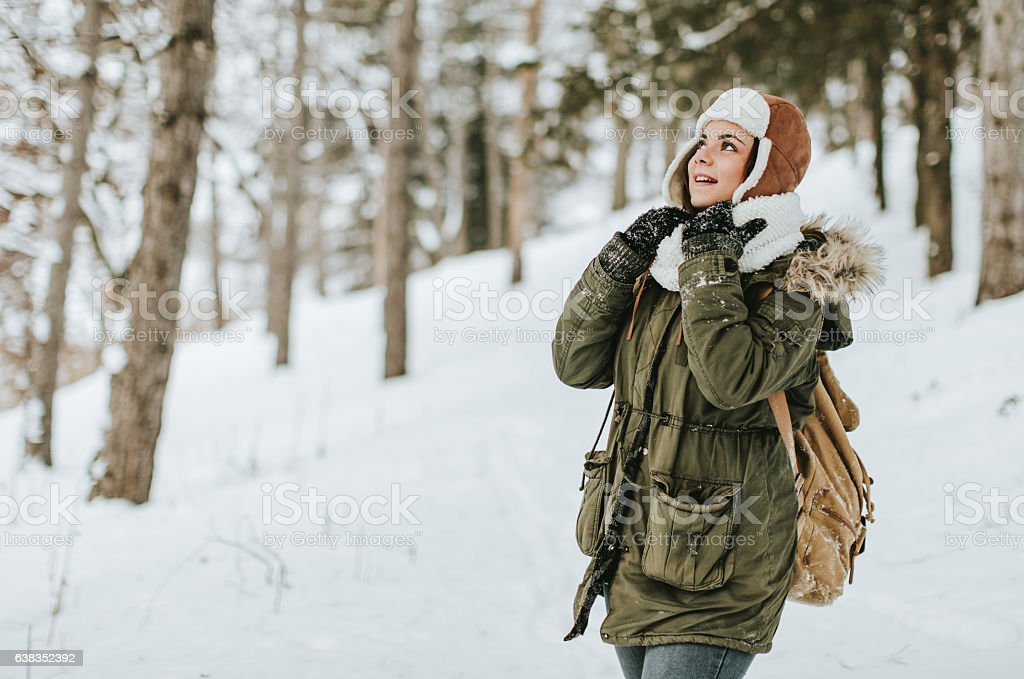 Young beautiful woman walking in winter park smiling stock photo