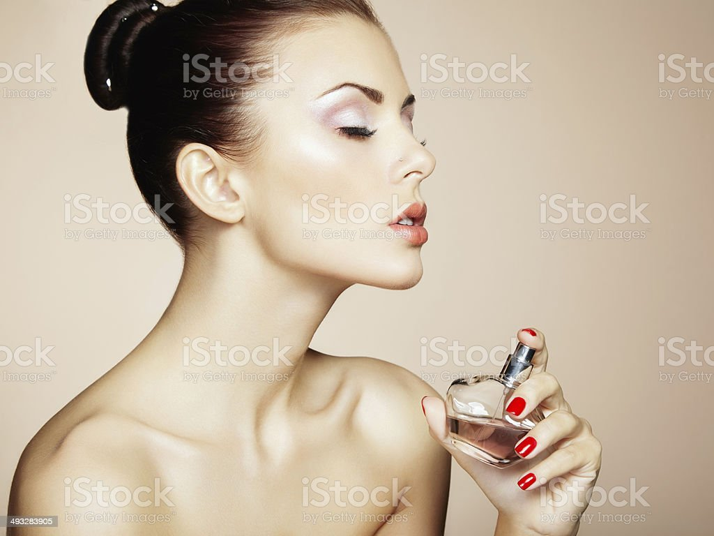 Young beautiful woman with bottle of perfume. Perfect Makeup stock photo