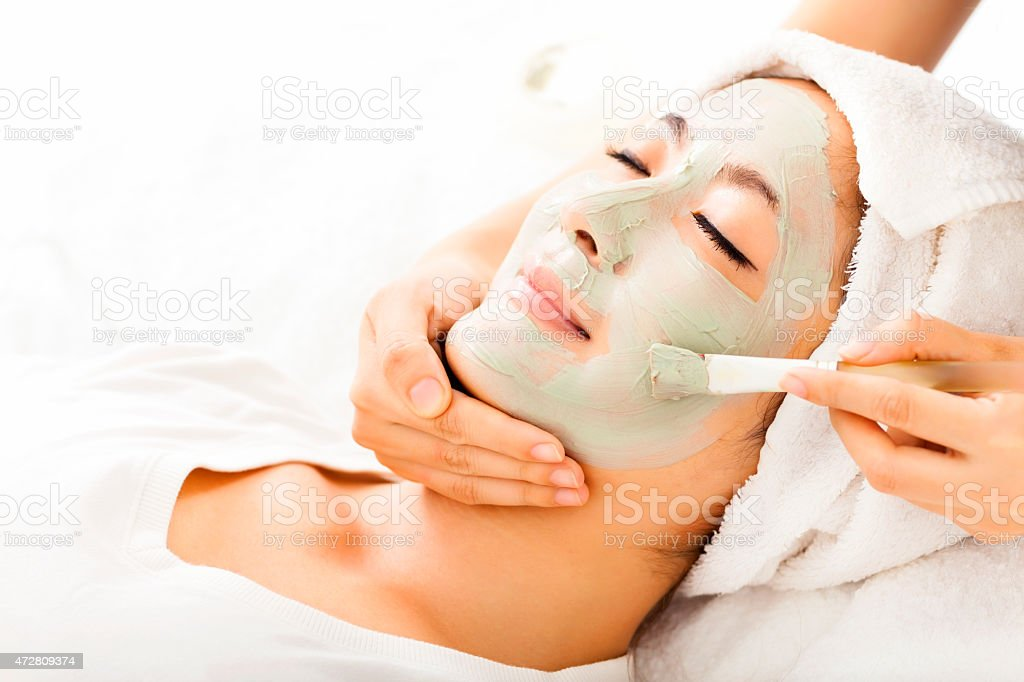 Young beautiful woman with clay facial mask stock photo