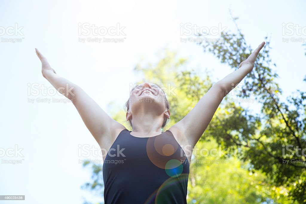 Young beautiful woman with hands raised in the park stock photo