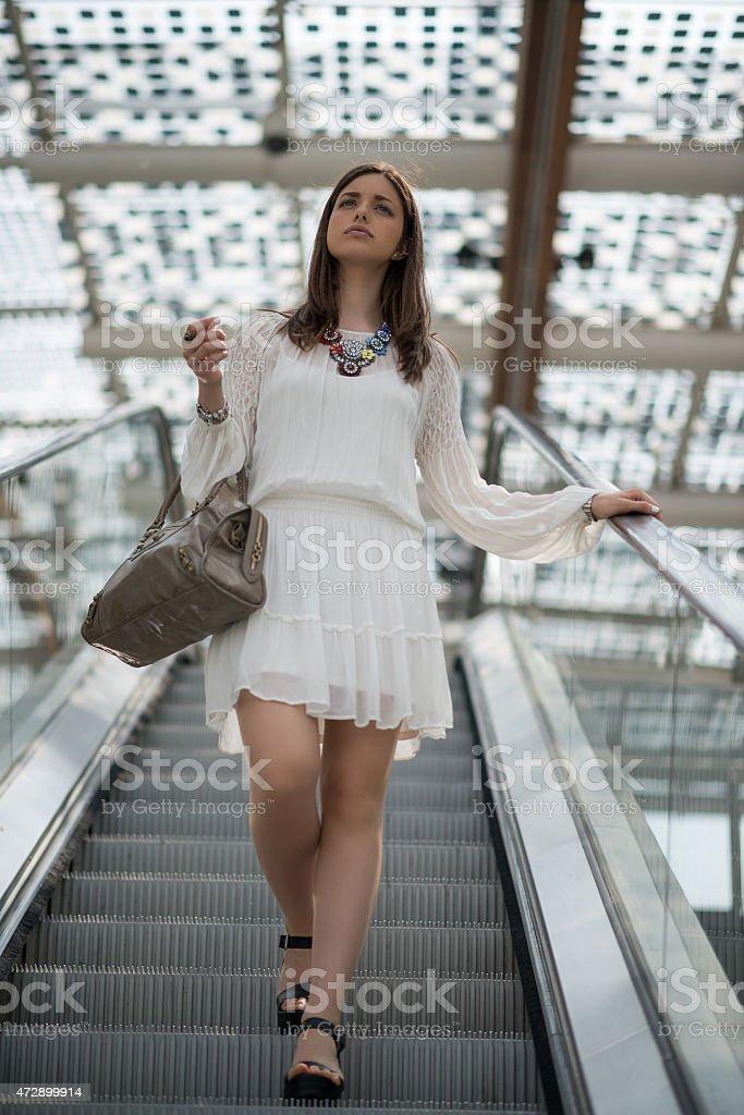 Young beautiful woman with white dress on escalator stock photo