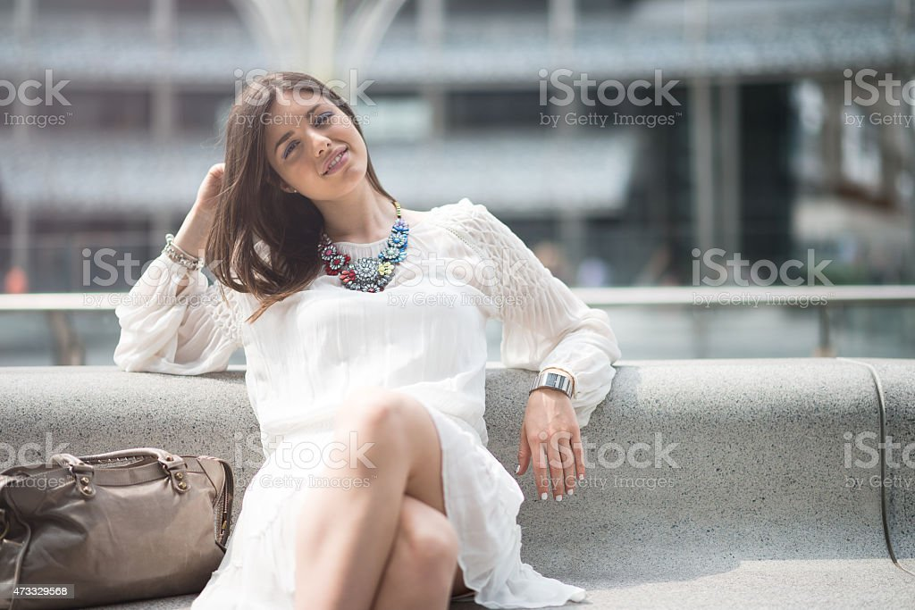 Young beautiful woman with white dress relaxing on bench stock photo