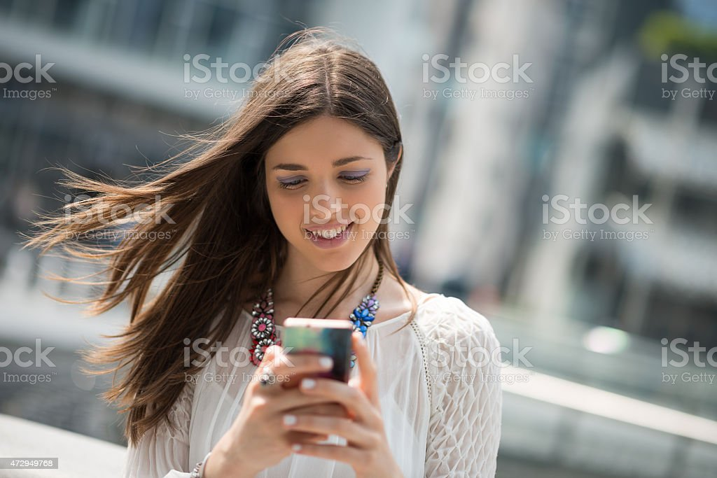Young beautiful woman with white dress using mobile smartphone stock photo