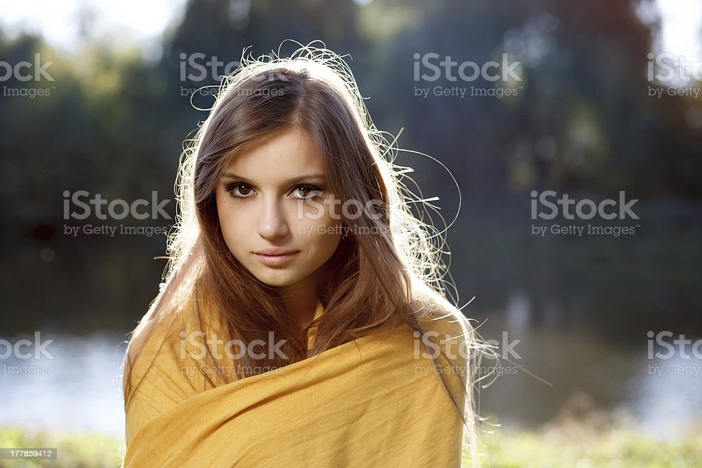 young beautiful woman wrapped herself up in a scarf stock photo